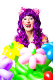 Female clown with colorful balloon flowers. Joyful posing female clown with colorful balloon flowers on isolated white Stock Image