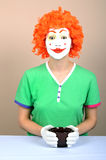 Female clown with cup. Half body portrait of young female clown with white face, orange hair and cup. Studio background Stock Photos