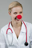 Female clown doctor with red nose. Isolated on gray Royalty Free Stock Image