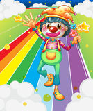 A female clown with flowers at the colorful road Royalty Free Stock Image