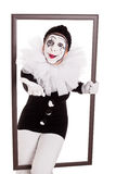 Female clown in a frame reaching hand to viewer Stock Images