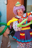 Female Clown Makes Balloon Hat For Kid. Tucker, GA, USA - July 28, 2012:  A female clown makes a balloon hat for a child at the Tucker Summer Festival in Stock Photography