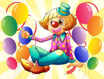 A female clown sitting in the middle of the balloons Stock Photos