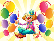 A female clown sitting surrounded with colorful balloons Royalty Free Stock Photos