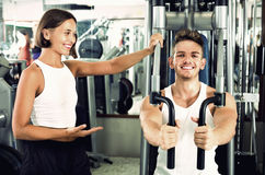 Female coach assisting man using fly machine Royalty Free Stock Photo