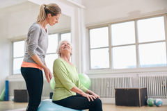 Female coach assisting senior woman exercising Stock Photos