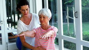 Female coach assisting senior woman in performing exercise. At home stock footage