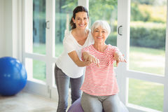 Female coach assisting senior woman in performing exercise Royalty Free Stock Photos