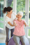 Female coach assisting senior woman in performing exercise Stock Images