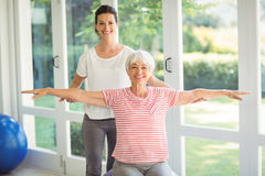 Female coach assisting senior woman in performing exercise. Female coach assisting senior women in performing exercise at home Royalty Free Stock Image