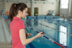 Female coach blowing whistle and looking at stopwatch near poolside Royalty Free Stock Photo