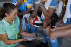Female coach discussing over clipboard with volleyball players Stock Photo