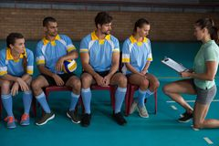 Coach discussing with volleyball players sitting on chairs Royalty Free Stock Image