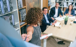 Female coach explaining project to business team in headquarters. Unrecognizable female coach explaining project management studies to business team at table in Royalty Free Stock Images