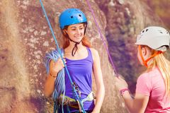 Female coach with girl preparing to rock climbing. Female coach with girl attached at harnesses preparing to rock climbing royalty free stock photos
