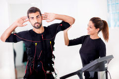 Female coach giving man ems electro muscular stimulation exerci Royalty Free Stock Image