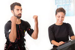 Female coach giving man ems electro muscular stimulation exercise