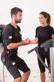 Female coach giving man ems electro muscular stimulation exercis Stock Photos