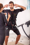 Female coach giving man ems electro muscular stimulation exercis Royalty Free Stock Image