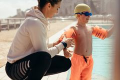 Boy at swimming class with trainer. Female coach helping boy put on sleeve floats by poolside. Woman putting sleeves floats on boy`s hand for swimming lessons at royalty free stock photos