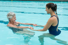 Female coach helping senior woman in swimming pool Stock Photography