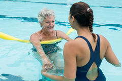 Female coach helping senior woman in swimming pool. Smiling female coach helping senior woman in swimming pool Royalty Free Stock Photo