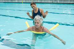 Female coach helping senior woman in swimming pool Royalty Free Stock Image