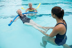 Female coach helping senior women in swimming pool. Smiling female coach helping senior woman in swimming pool Royalty Free Stock Photo