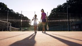 Female coach and her female pupil walking on the court. stock video footage