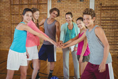 Female coach and high school kids with their hands stacked Royalty Free Stock Photo