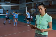 Coach holding clipboard at volleyball court Royalty Free Stock Image
