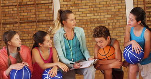 Female coach mentoring high school kids. In basketball court stock video footage