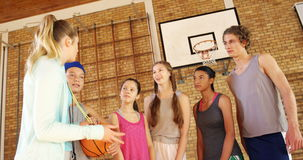 Female coach mentoring high school kids. In basketball court stock video