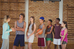 Female coach mentoring high school kids in basketball court Royalty Free Stock Photo
