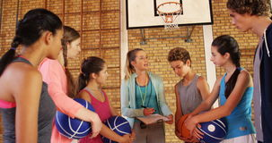 Female coach mentoring high school kids. In basketball court stock footage