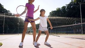 Female coach teaching little girl playing tennis on the court. stock video