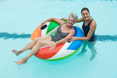 Female coach and senior woman smiling in swimming pool Royalty Free Stock Photography