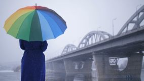 Female in coat with rainbow umbrella during snow. Sad female in blue coat standing holding rainbow colors umbrella in winter during snow. Urban bridge on the stock video footage