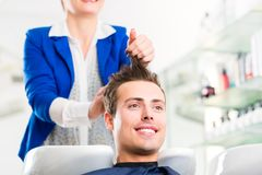 Hairdresser advice man on haircut in barbershop. Female coiffeur washing men hair in hairdresser shop royalty free stock photography