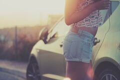 Female in Coke Shirt and Jean Shorts by Car Royalty Free Stock Photos