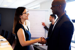Female colleague shaking hands with male colleague Royalty Free Stock Images