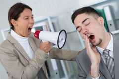 Female colleague shouting at sleepy worker Royalty Free Stock Photos