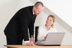 Female colleague showing male coworker something. Nice office setting with wooden table and two coworkers. Female colleauge showing male something on the grey Stock Image