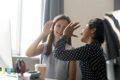 Female colleagues celebrate business win, giving five. Female smiling colleagues celebrate business win, goal achievement at workplace, giving five, successful stock photography
