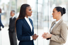 Female colleagues conversation. Successful female colleagues having conversation in office royalty free stock photos