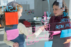 Female colleagues giving handshake seen through glass. Female colleagues giving handshake at creative office seen through glass Stock Photography