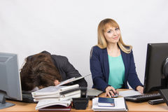 Female colleagues in the office, one had fallen asleep on a pile of folders, the other works in the computer and looked in the fra Stock Photos