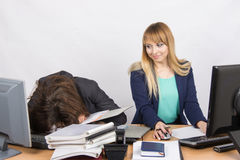Female colleagues in the office, one had fallen asleep on a pile of folders, and the second looked at her Stock Photography