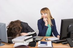 Female colleagues in the office, one had fallen asleep on a pile of folders, the second with a sneer looks at her Royalty Free Stock Images