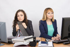 Female colleagues in the office, a tired looking in the monitor, the other happy working on a computer Royalty Free Stock Image